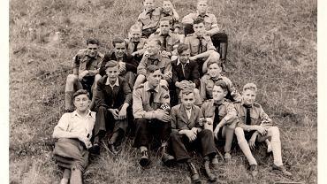 Grupa młodzieży, częściowo w mundurach Hitlerjugend. Noszenie mundurów przez członków nazistowskich organizacji młodzieżowych - Hitlerjugend i Bund Deutscher Mädel były demonstracją przynależności do narodowosocjalistycznej wspólnoty. Poza nią pozostawali tzw. swingsi (od swingu, który z upodobaniem tańczyli), którzy także strojem manifestowali swoją odrębność. Preferowali ekscentryczną, ostentacyjnie elegancką odzież (o ile rodzice za nią płacili): zamiast hitlerjugendowskich krótkich spodenek woleli garnitury z doskonałej wełny i jedwabne krawaty, szale i eleganckie parasole. Wystawa 'Glanz und Grauen. Mode im Dritten Reich' (Blask i groza. Moda w Trzeciej Rzeszy) w Państwowym Muzeum Przemysłu Tekstylnego (Staatliches Textil- und Industriemuseum) w Augsburgu.