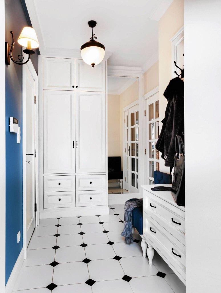 Na podłodze ułożono ośmioboczne białe płytki z czarnymi wstawkami w stylu retro (kolekcja Mugat firmy Vives). Takie same gospodarze wybrali do kuchni. Pod sufitem zamocowano sztukaterię. Lustro od podłogi do sufitu stwarza złudzenie, że przedpokój ciągnie się w głąb mieszkania. Pani domu może swobodnie przeglądać się od stóp do głów.
