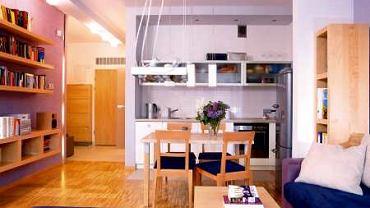 Aneks kuchenny jest integralną częścią salonu. Jasne, gładkie fronty szafek i przeszklone witrynki dają wrażenie lekkości, nie przytłaczają więc wnętrza.