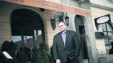 Zbigniew Kocyk przed kawiarnią literatów. Nad nim markiza do likwidacji, za nim tuje do wyrzucenia