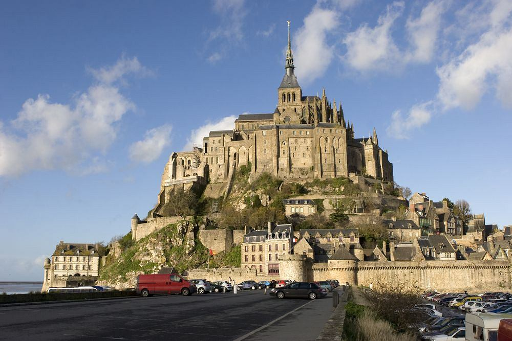 Mont Saint Michel. Niezwykłe opactwo i miasteczko w Normandii to jedna z największych atrakcji Francji, rocznie odwiedzana przez 3 miliony turystów (popularniejsze są tylko wieża Eiffla i Wersal). Leży na skalistej wyspie połączonej ze stałym lądem tylko wąską groblą. Już z wielu kilometrów widać wyniosłe wzgórze, zwieńczone romańsko-gotyckim klasztorem z iglicą sięgającą 150 m n.p.m.