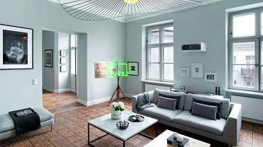 Mimo zróżnicowanych wzorów podłogi przestrzenie salonu ijadalni harmonijnie się przenikają. Łączy je perłowa szarość ścian, biel sufitów ilistew przypodłogowych. Wieczorami lampa wisząca Vertigo (proj. Constance Guisset, NAP) reżyseruje spektakularny teatr światłocienia.