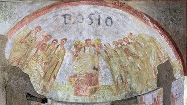 Na fresku widać Jezusa siedzącego na tronie. Po obu jego bokach stoją apostołowie. To, co przyciąga uwagę, to twarz Jezusa - nie ma na niej zarostu