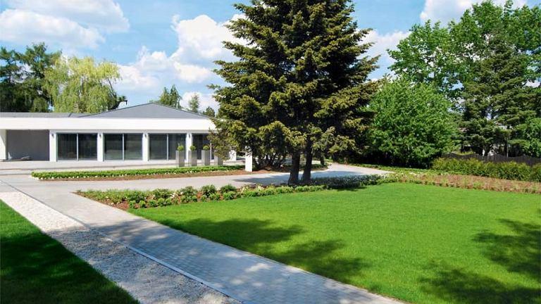 Wbrew pozorom dom jest dwupoziomowy (z poziomem -1). Otoczony rozległą zielenią rozrośnie się niebawem o kolejną działkę i bliźniaczą