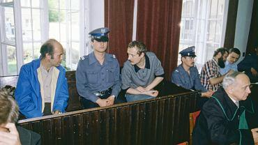 Sąd Okręgowy w Warszawie, 13 lipca 1984 r. Na ławie oskarżonych siedzą Jacek Kuroń i Adam Michnik (rozdziela ich milicjant), a w głębi widać Henryka Wujca (z brodą) i Zbigniewa Romaszewskiego. Mieli być sądzeni pod zarzutem przygotowywania obalenia ustroju PRL siłą, za co groziło do 10 lat więzienia.