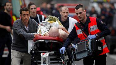 Jedna z rannych ofiar strzelaniny w redakcji tygodnika transportowana do karetki