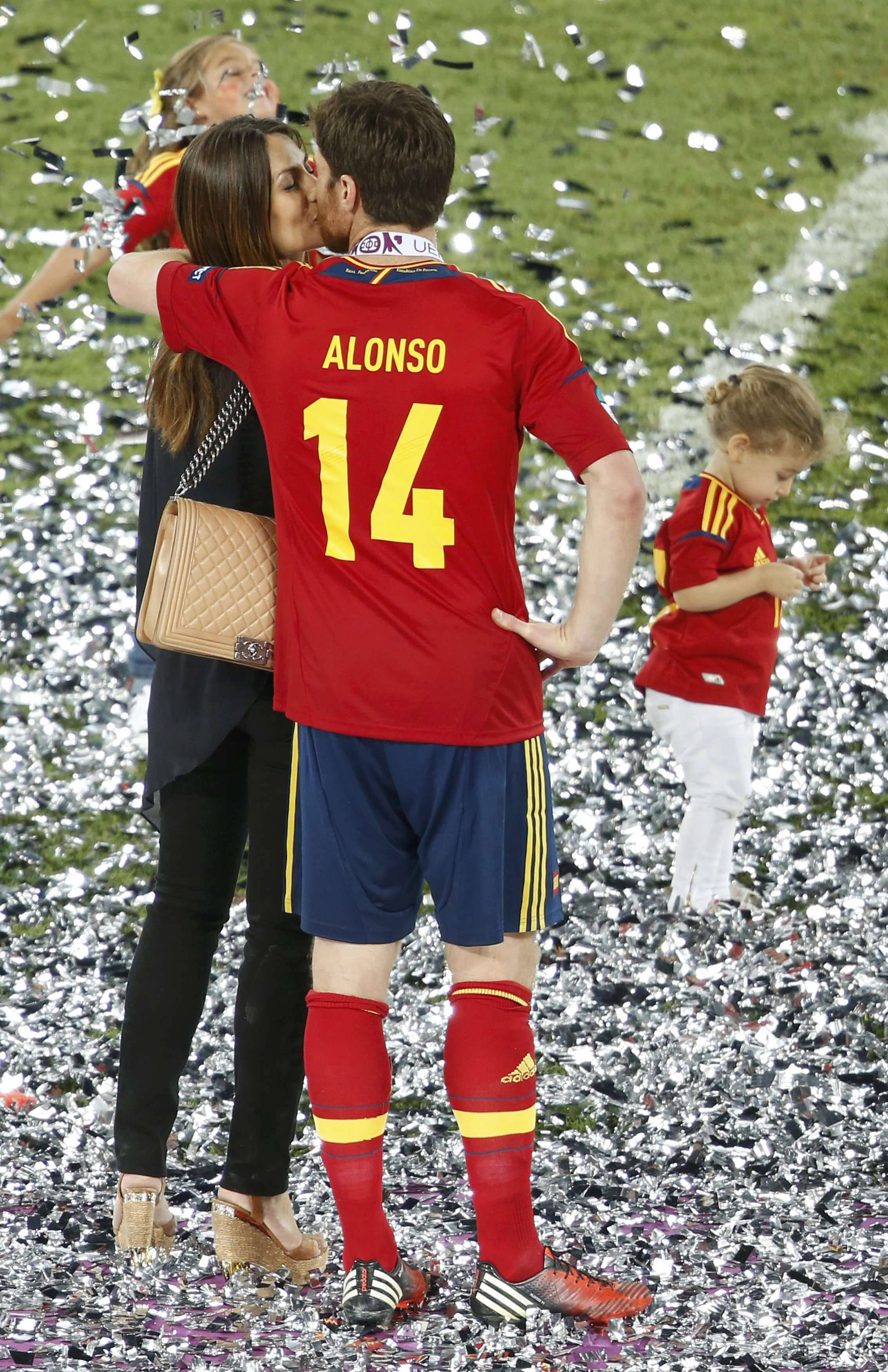 Spain's Xabi Alonso kisses his wife Nagore on the pitch after defeating Italy to win the Euro 2012 final soccer match at the Olympic stadium in Kiev, July 1, 2012. REUTERS           REUTERS/Charles Platiau (UKRAINE  - Tags: SPORT SOCCER TPX IMAGES OF THE DAY)