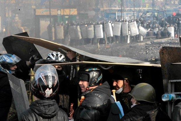 Demonstranci kryj� si� przed ostrza�em ze strony milicji - jej oddzia�y widoczne s� na drugim planie