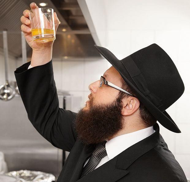 Szalom Ber Stambler rabin pokazuje jak jego współpracownicy rozbijają jajka w szklance i dokładnie oglądają je z każdej strony