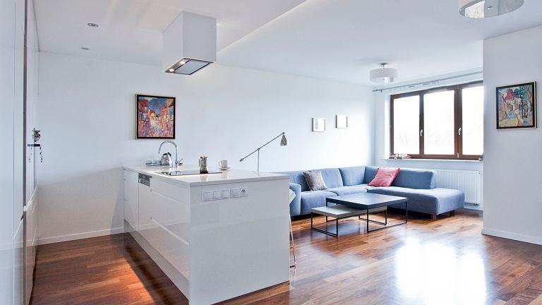 Punktem centralnym strefy dziennej jest pokaźnych rozmiarów wyspa, która umownie oddziela kuchnię od salonu. Podwieszany sufit z modernistycznym okapem również zaznacza, gdzie się kończy miejsce kuchennych działań.