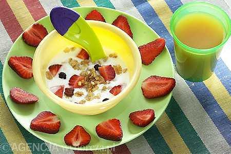 Jogurt naturalny z muesli owocowym i truskawkami pokrojonymi w plasterki