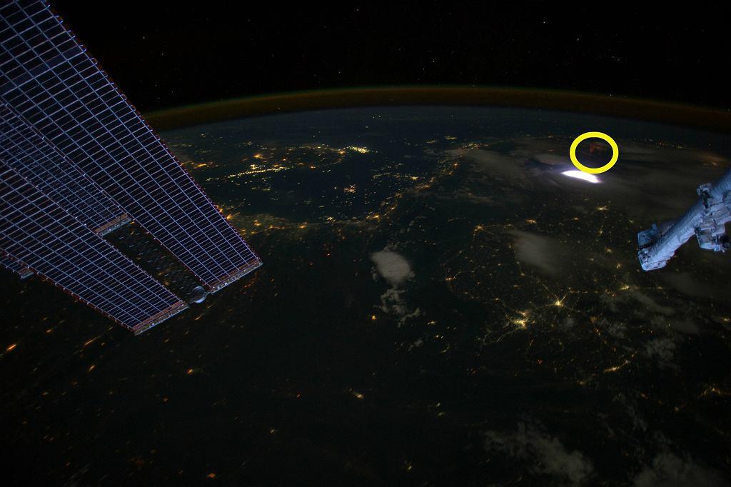 Zdjęcie wykonane w 2012 roku z pokładu Międzynarodowej Stacji Kosmicznej. Nad widoczną na zdjęciu, rozświetlającą chmury błyskawicą, widać charakterystycznego czerwonego 'duszka' (sprite)