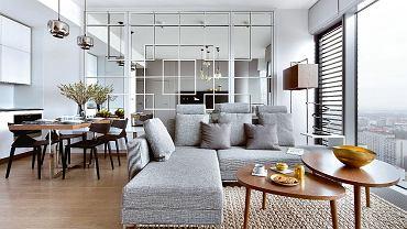 Minimalistyczna kuchnia z jadalnią (stół Stylhen, krzesła Arper) przechodzą płynnie w strefę salonu. Ścianę wypełniają tafle lustrzane w prostych ramach, które tworzą dekorację w japońskim stylu.