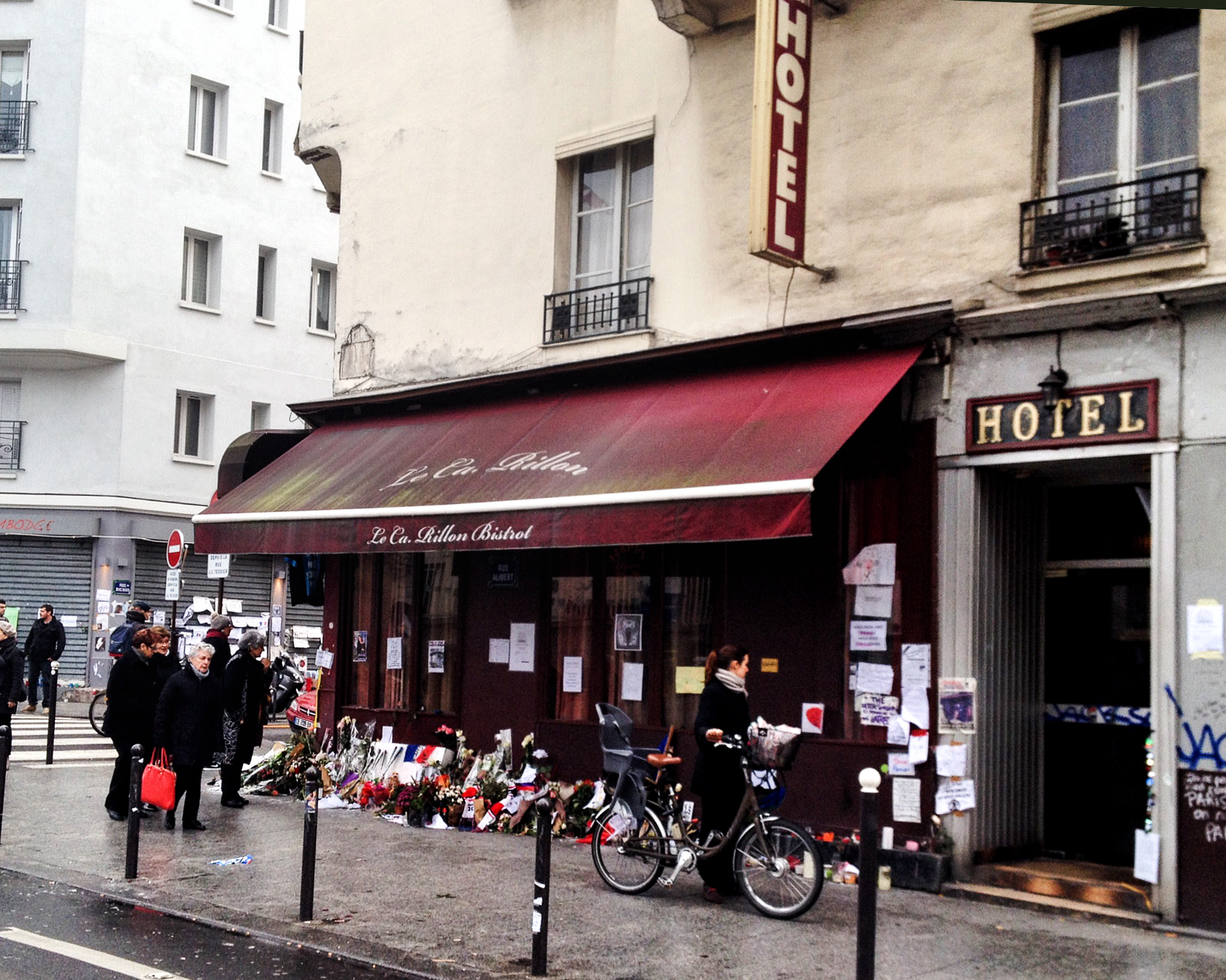 Le Carillon po zamachach. Pod zaatakowaną kawiarnią wciąż palą się światła a przechodnie składają kwiaty (fot. Ana Brzezińska)