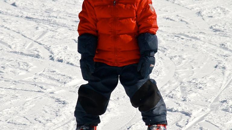 Mały narciarz ubrany adekwatnie do sytuacji