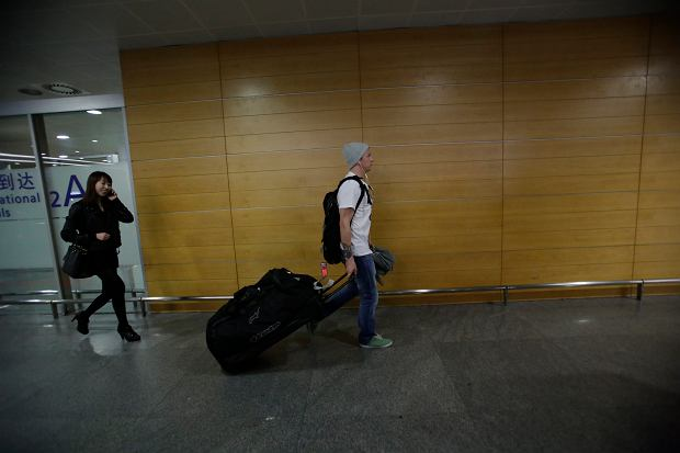Lotus driver Kimi Raikkonen of Finland walks away from the arrival hall upon his arrival at Pudong International Airport ahead of Chinese Formula One Grand Prix in Shanghai, China Thursday, April 11, 2013. (AP Photo/Eugene Hoshiko)
