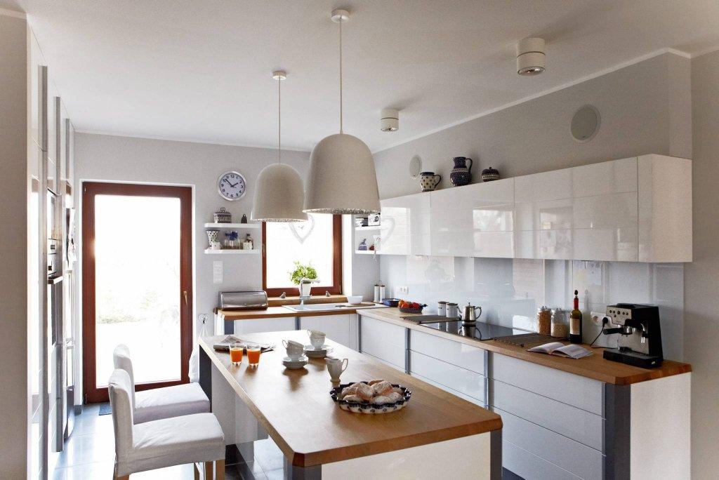 Kuchnię zaprojektowano tak, aby każda rzecz miała swoje miejsce. Utrzymaniu porządku służą liczne szafki dolne i górne oraz w wyspie i wysokiej zabudowie, zajmującej jedną ze ścian.