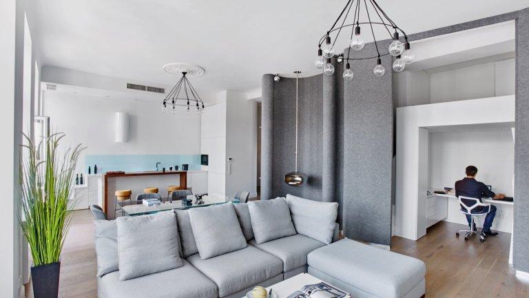 Domowe biuro jest jednym ze znaków szczególnych mieszkania. Architekt zaprojektował nad nim antresolę z dodatkowym miejscem do spania, a całość można zasłonić przesuwając filcowe panele. W jednym z miękkich załamań