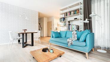 W salonie główną rolę odgrywa sofa w wyszukanym, błękitnym odcieniu.
