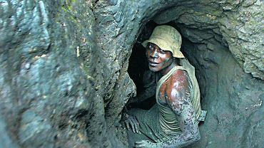 Kopalnia kobaltu. Mężczyzna schodzi do tunelu wykopanego łopatami. Kopalnia kobaltu w Shinkolobwe, 35 km od miasta Likasi w Demokratycznej Republice Konga