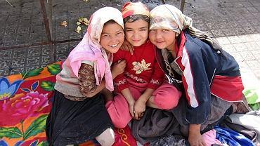 Walec drogowy z chińską flagą miażdży grupę Ujgurów w muzułmańskich strojach. Innych rozrąbuje siekiera z chińskim godłem
