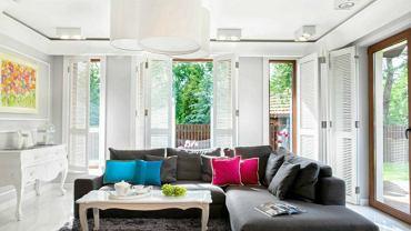 W tym salonie główna rolę odgrywa duża narożna sofa. W białym i przestronnym wnętrzu prezentuje się naprawdę dobrze.