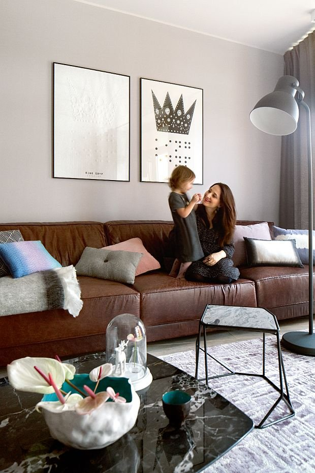 Na pokrytej skórą sofie (proj. Poco Design) właścicielka z córeczką Lilią. Ażurowy stolik The Prime, Henge; stolik kawowy z kamiennym blatem, The Prime, Busnelli, grafiki autorstwa Jaremy'ego Drogowskiego.