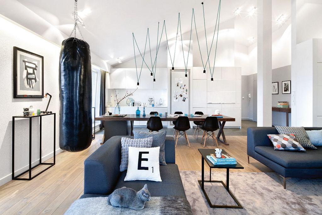 W przestrzeni salonu połączonego z kuchnią i jadalnią zwracają uwagę akcenty graficzne: ażurowe stoliki, krzesła oraz pajęcza konstrukcja lampy nad stołem. Najmocniejszy stanowi worek treningowy pana domu.