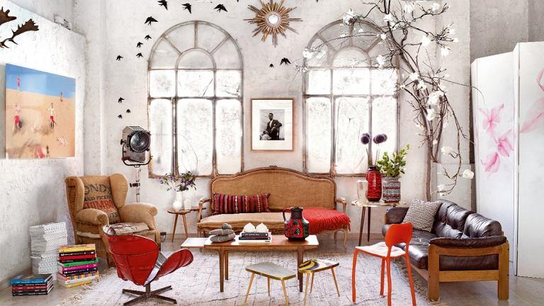 Ludwikowska sofa tapicerowana lnem, stary fotel obity jutowym workiem, reinterpretacja słynnego obrotowego krzesła Swan Arne Jacobsena, wykonana z beczek po benzynie przez firmę PO!Paris. Między oknami zdjęcie malijskiego fotografa Seydou Keity.