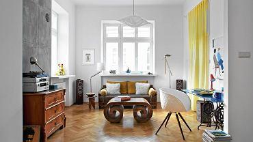 Śmiałe połączenie: indyjską sofę (najnowszy nabytek) istolik gospodarz zestawił zkomodą kupioną na warszawskim targu staroci (na niej stoi sprzęt audio) oraz designerskim krzesłem Structure projektu Przemysława 'Mac' Stopy (Dobra Showroom). Na parapecie  po lewej - chiński kot Maneki-neko przysłany  zAmsterdamu.