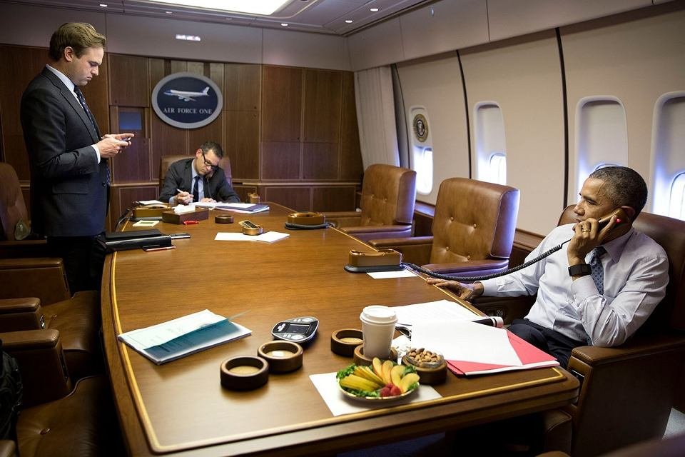 Prezydent USA Barack Obama rozmawia przez telefon z premierem Izraela Beniaminem Netanjahu. Rozmowie przysłuchuje się doradca Colin Kahl (z tyłu). Air Force One, gdzieś nad Louisville, USA,  2 kwietnia 2015 r.