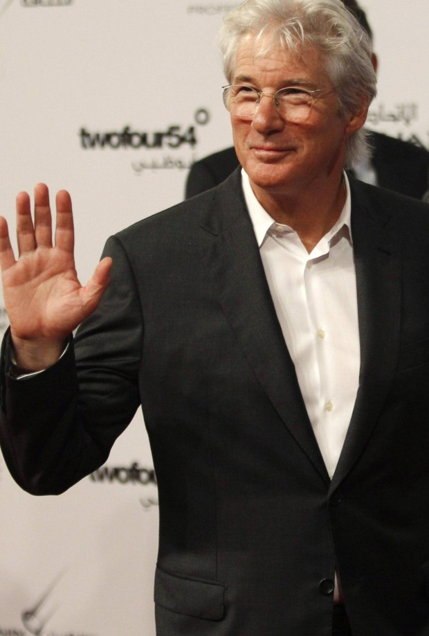 U.S. actor Richard Gere arrives on the red carpet during the opening of the Abu Dhabi Film Festival October 11, 2012. REUTERS/Ahmed Jadallah (UNITED ARAB EMIRATES - Tags: ENTERTAINMENT)