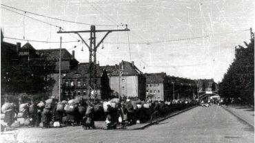 Niemcy opuszczają Szczecin. Zdjęcie wykonano w 1946 roku na ulicy Mickiewicza, zaraz za wiaduktem kolejowym. Tu polska administracja utworzyła 'Punkt zborczy nr 3'. Oczekujący na transport w głąb Niemiec Niemcy lokowani byli w dwóch budynkach. Na nieczynnych torach tramwajowych stanęły dwa baraki. W jednym była kuchnia, w drugim punkt dezynfekcji. Całość otoczona została ogrodzeniem z drutu. Stąd Niemcy maszerowali pod eskortą na stację Turzyn, gdzie oczekiwały na nich pociągi jadące do Lubeki. Punkt Zborczy Nr 3 zlikwidowano na początku października 1946 roku. Przeszło przez niego ponad 166 tys. Niemców w 101 transportach kolejowych.