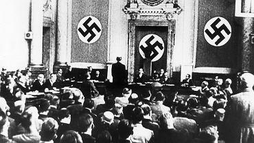 Trybunał Ludowy wydawał wyroki w gmachu dawnego gimnazjum przy Bellevuestrasse 15, koło placu Poczdamskiego w Berlinie. Jednak spiskowców z 20 lipca 1944 r. sądzono w gmachu Kammergericht, czyli berlińskiego sądu najwyższego. Rozprawy przeniesiono dlatego, że wielka i bogato zdobiona sala dawała większe możliwości uzyskania efektu propagandowego i mogła także pomieścić więcej widzów. Rozprawy nagrywano i pokazywano w kronice filmowej. Dla techników problemem było zachowanie Rolanda Freislera, który tak krzyczał na oskarżonych, że trzeba było bardzo ściszać mikrofony. Od swego powstania w 1934 r. Trybunał Ludowy wydał ponad 16 tys. wyroków. Co trzeci to kara śmierci. Na zdjęciu zrobionym 15 sierpnia 1944 r. Freisler przesłuchuje Adama von Trotta zu Solz, jednego z uczestników spisku z 20 lipca.