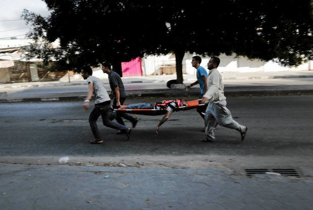 Ranny niesiony na noszach do karetki w mie�cie Gaza