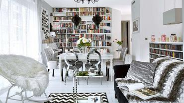 Wszechobecna biel: wtym kolorze są ściany, podłogi iwiększość mebli; właściciele przemalowali nawet pianino! Na takim neutralnym tle dobrze prezentuje się kolekcja książek, płyt iobrazów. Żyrandol, kupiony wjednym zmarketów budowlanych, winnym wnętrzu mógłby wydać się pretensjonalny. Tu świetnie pasuje do stylizowanego stołu (IKEA) oraz srebrzystych krzeseł wstylu glamour. Głównym bohaterem salonu jest zrobiona na zamówienie biblioteczka. Boczne półki są ścięte, dzięki czemu tworzą spójną całość ze skośną ścianą.