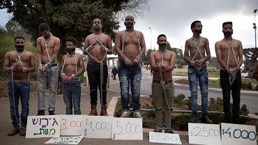Imigranci z Erytrei w łańcuchach symbolizujących niewolnictwo demonstrują przed Knesetem, izraelskim parlamentem, przeciwko deportacjom do Ugandy i Rwandy. Jerozolima, 17 stycznia 2018 r.