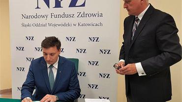 Janusz Buda, wiceprezydent Jastrzębia-Zdroju, podpisuje kontrakt w obecności Jerzego Szafranowicza, dyrektora śląskiego oddziału NFZ
