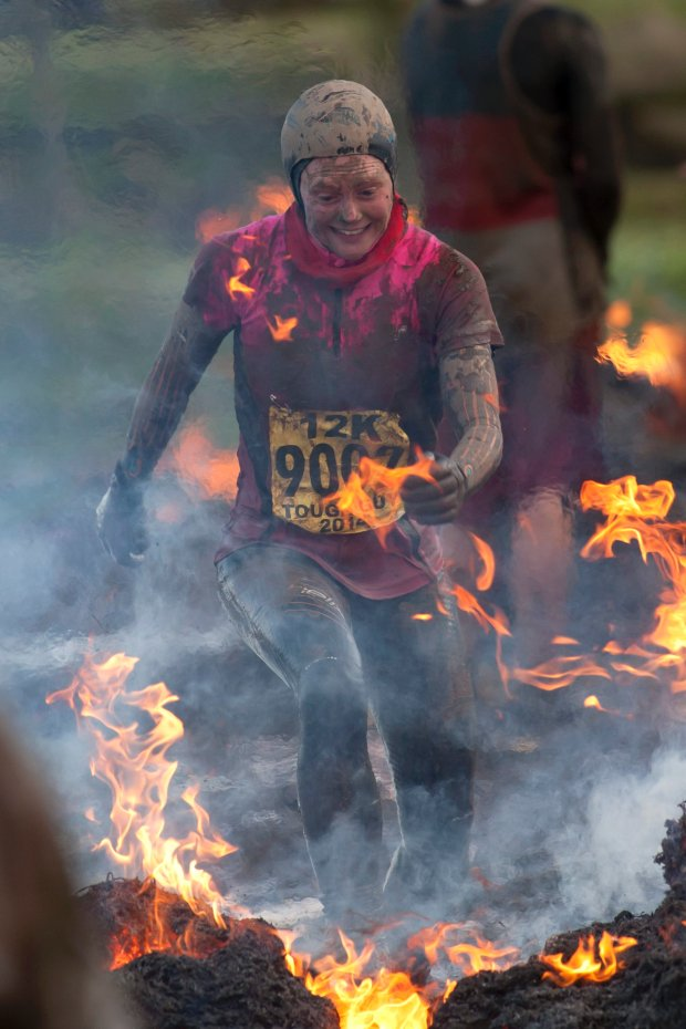 A competitor jumps through fire during the annual Tough Guy race - the toughest race in the world