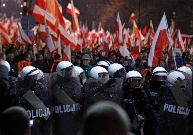 Riot policemen cordon off far-right protesters during the annual far-right march, which coincides with Polands national Independence Day in Warsaw November 11, 2013. Polish riot police used rubber bullets on Monday to break up groups of masked far-right youths who threw firecrackers and set fire to parked cars during a nationalist march through the centre of the capital. REUTERS/Kacper Pempel (POLAND  - Tags: POLITICS CIVIL UNREST)