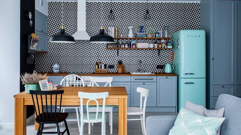 Minimalizm szarej zabudowy w kuchni i przedpokoju przełamują kolorowe akcenty - lodówka marki Smeg, niebieska ściana, tekstylne dodatki.