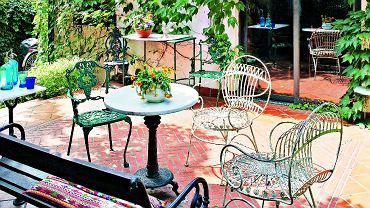 Na tarasie jak wrzymskim patio: terakotowa posadzka, kute białe fotele zWłoch, stolik zkamiennym blatem (wyciętym przez zaprzyjaźnionego artystę).