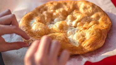 Langosze to złociste węgierskie placki drożdżowo-ziemniaczane smażone na oleju i podawane zwykle ze śmietaną i startym żółtym serem