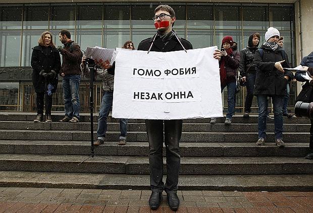 Działacz uczestniczący w wiecu w obronie praw rosyjskich gejów i lesbijek w Petersburgu trzyma plakat z napisem