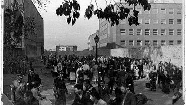 Na fotografii z 1942 r. widać ul. Stawki i obładowanych mieszkańców getta, którzy idą w kierunku rampy kolejowej, na tyłach budynków po lewej stronie zdjęcia. Niemcy nazwali to miejsce Umschalgplatzem (placem przeładunkowym). Ludzie za chwilę wsiądą do bydlęcych wagonów i odjadą do Treblinki. Niemieccy strażnicy Umschlagplatzu mieli siedzibę w jasnym gmachu po prawej stronie. Budynki ze zdjęcia, istnieją do dziś. W tych po lewej mieści się m.in. Zespół Szkół Licealnych i Ekonomicznych nr 1, a po prawej - Wydział Psychologii UW.