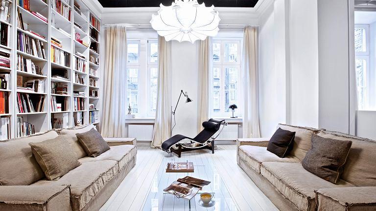 Okna salonu wychodzą na dziedziniec. Między nimi ustawiono szezląg LC4 - ikonę designu (proj. Le Corbusier). Ścianę po lewej stronie zajmuje biblioteka projektu właścicielki, lampa wisząca Zeppelin, proj. Marcel Wanders (Flos).