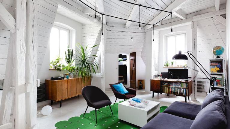 Współczesne meble Grzegorz, właściciel poddasza, zestawił z meblami sprzed kilkudziesięciu lat własnoręcznie odrestaurowanymi. Dywan w żywym odcieniu zieleni pełni rolę akcentu barwnego ożywiającego graficznie pomyślaną przestrzeń.