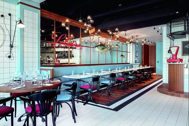 Wieloosobowa tapicerowana kanapa pod ścianą luster nawiązuje do ławek wzdłuż sopockiego molo.