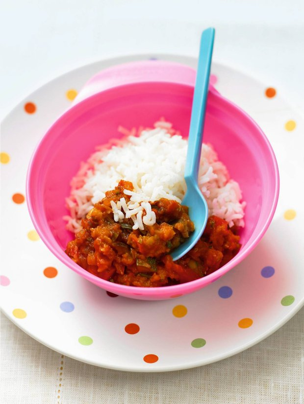 Ratatouille with rice in pink bowl, elevated view, close up