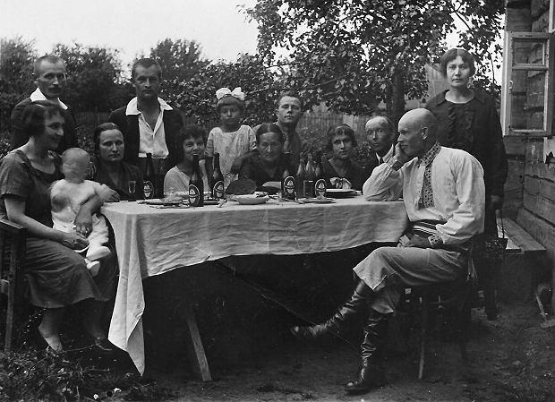 Butelki piwa lwowskiego na stole podczas spotkania towarzyskiego, okres międzywojenny. Reklamy zachęcały do picia piwa, by 'radość kwitła dziś w rodzinnym kole'.